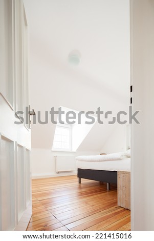 Low angle view through the white painted door into a loft bedroom with a sloping white ceiling, a wooden parquet floor and double bed - stock photo