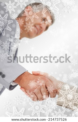 Low angleshot of a hand shake against snowflakes on silver - stock photo