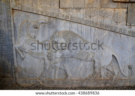 Low (bas) relief in Persepolis, Iran, lion attacking bull - stock photo