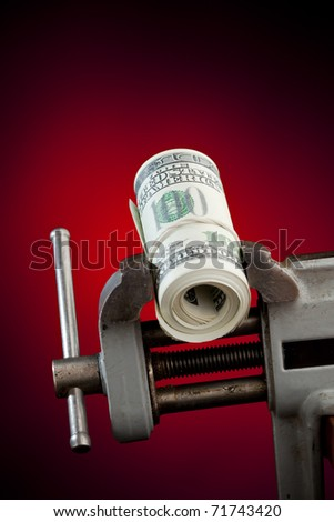 low budget concept - money in the vice tool - stock photo