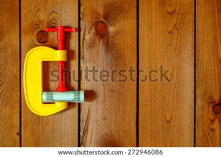 Low budget or financial crisis concept - money in the vice tool - stock photo