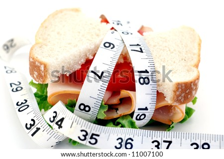 Low-carb concept with a turkey sandwich and tape measure over a white background