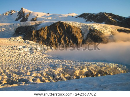 Low Clouds Drift Over the Fox Glacier Just Before Sunset, South Island of New Zealand - stock photo