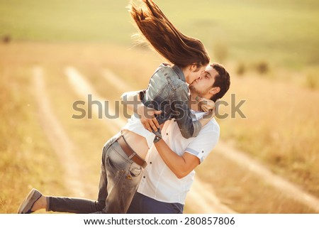 low contrast portrait of a happy loving couple walking outdoor in the autumn or summer field, portrait in warm colors