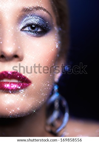 Low depth of focus portrait of beautiful young woman with vogue shining sparkle face makeup