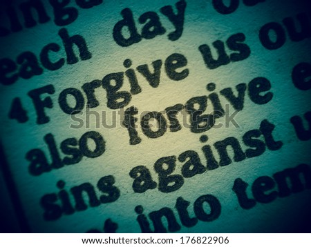 "Low DOF macro shot of a Bible text from the Gospel of Luke chapter 11 verse 4 with the words of Jesus called the Lord�´s Prayer: ""Forgive us our sins as we forgive those who sin against us""."