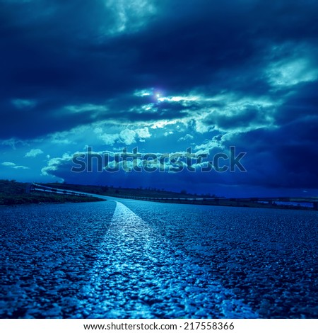low dramatic clouds over asphalt road in dark blue moonlight - stock photo