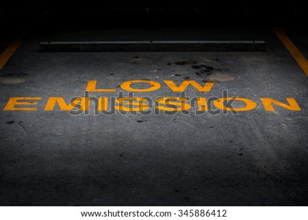 Low Emission yellow word on asphalt parking lot. - stock photo