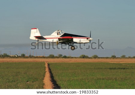 Low flying crop duster or agricultural aircraft over field.
