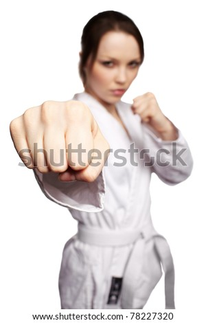low focus isolated portrait of beautiful martial arts girl in kimono excercising karate kata. focus on fist. - stock photo