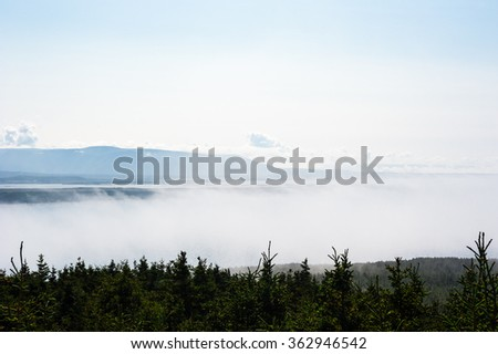 Low fog and clouds with tops of evergreen trees in foreground and mountain range in background, in Newfoundland, Canada. - stock photo
