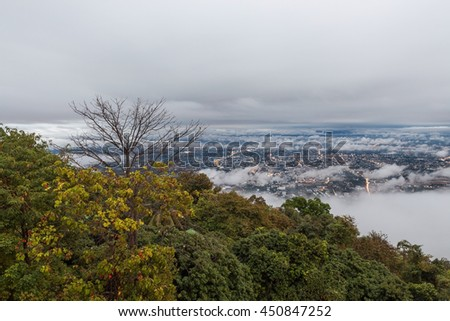 Low gray cloudy sky above Chiang Mai city in Northern Thailand, view from Doi Suthep. City lights in the twilight under the scattered clouds with tropical forest on the foreground. - stock photo