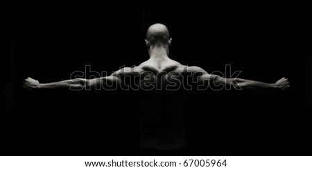 Low key artistic strong man on a black background