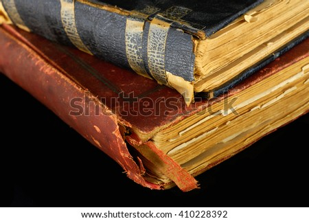 Low key close-up of very old books in poor condition on black background. There are two books. One has tape residue on the binding. The pages are yellowed with age. - stock photo