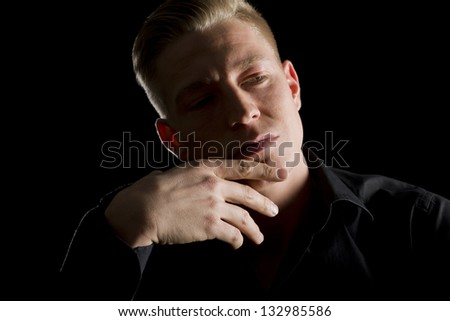 Low-key close up portrait of young serious man in dark shirt with hand at chin looking aside, isolated on black background.