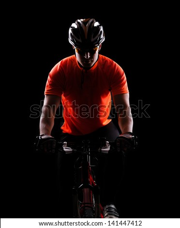 low key color silhouette of a cycling man black background - stock photo
