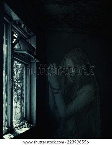 low key halloween horror scene. Sad scary transparent blurred woman ghost praying about window in old house