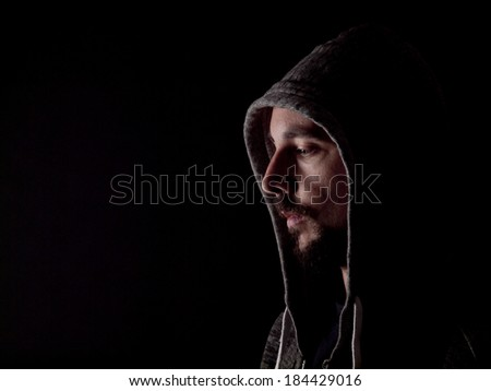 Low key image of a bearded man with a hoody - stock photo