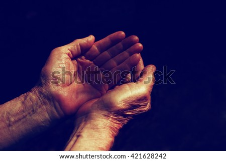 low key image of male Wrinkled old hands begging asking for money, help, reaching out and compassion concept  - stock photo