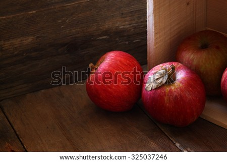 low key image of red apples over wodden textured table - stock photo