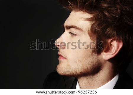 low key image of side profile of a young man - stock photo