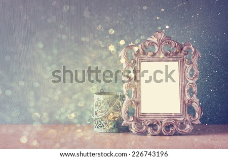 low key image of vintage antique classical frame and Burning candle on wooden table and glitter lights background . filtered image  - stock photo