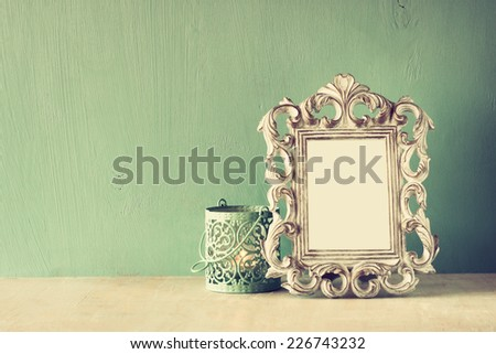 low key image of vintage antique classical frame and open Lantern on wooden table. filtered image  - stock photo
