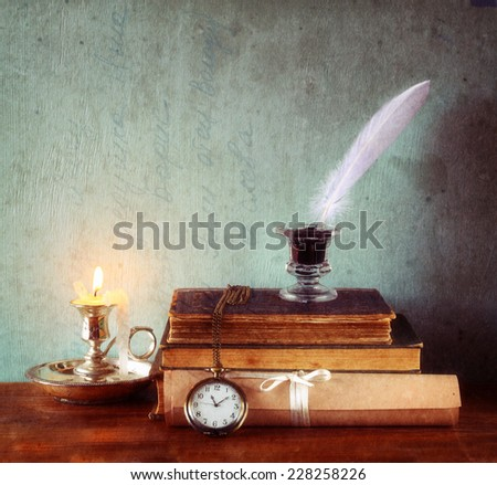 low key image of white Feather, inkwell and ancient books on old wooden table. image textured  - stock photo