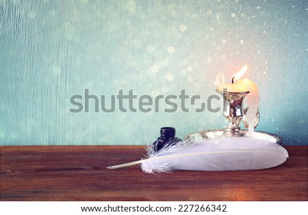 low key image of white Feather, inkwell, scroll and  glitter lights background on old wooden table - stock photo