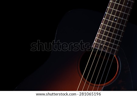 low key image showing part of sunburst acoustic guitar & beautiful rim light of six strings,frets and body shape , isolated on black + copy space for music concept background - stock photo