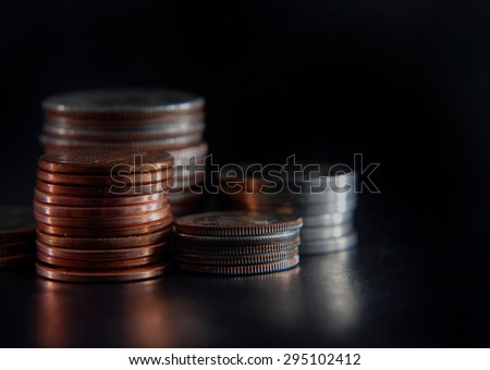 Low key macro image of randomly stacked United States coins on black background and rough, glossy table lit from the side. Strong shadows enhance the rough appearance of the used money. Copy space. - stock photo