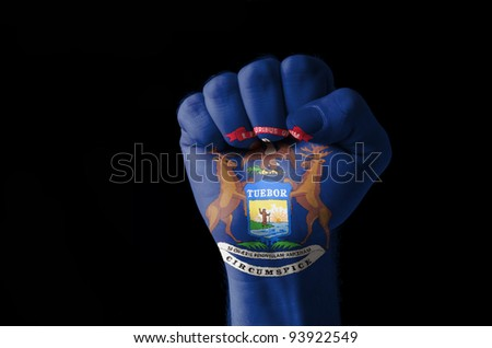 Low key picture of a fist painted in colors of american state flag of michigan