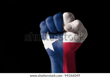 Low key picture of a fist painted in colors of american state flag of texas - stock photo