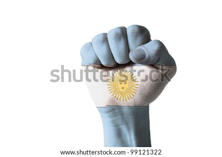 Low key picture of a fist painted in colors of argentina flag - stock photo