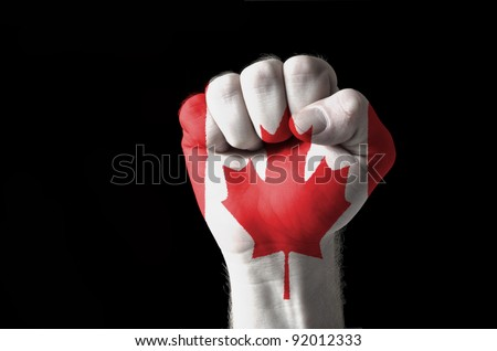 Low key picture of a fist painted in colors of canada flag - stock photo