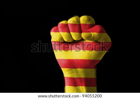 Low key picture of a fist painted in colors of catalonia flag - stock photo