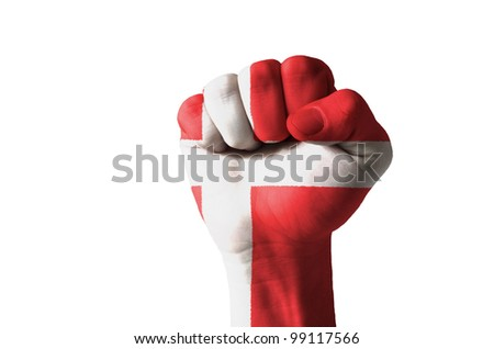 Low key picture of a fist painted in colors of denmark flag - stock photo