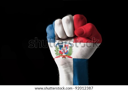 Low key picture of a fist painted in colors of dominican republic flag - stock photo