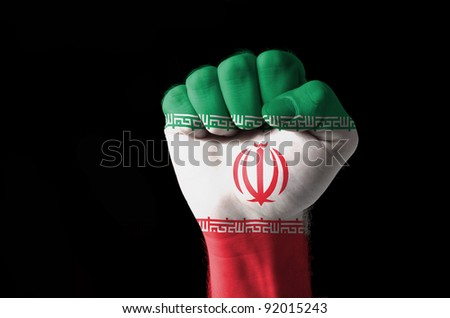 Low key picture of a fist painted in colors of iran flag - stock photo