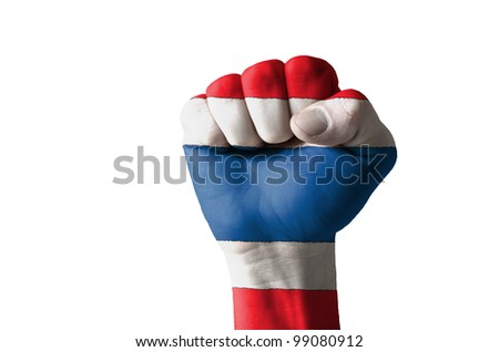 Low key picture of a fist painted in colors of thailand flag - stock photo