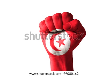 Low key picture of a fist painted in colors of tunisia flag - stock photo
