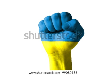 Low key picture of a fist painted in colors of ukraine flag - stock photo