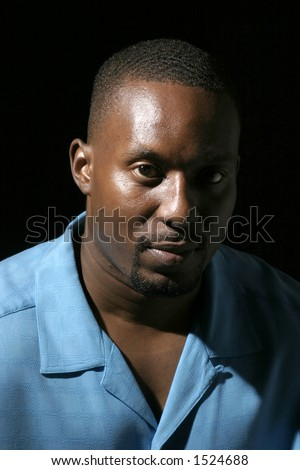Low key portrait headshot on black background of a handsome African American male with a serious expression. - stock photo