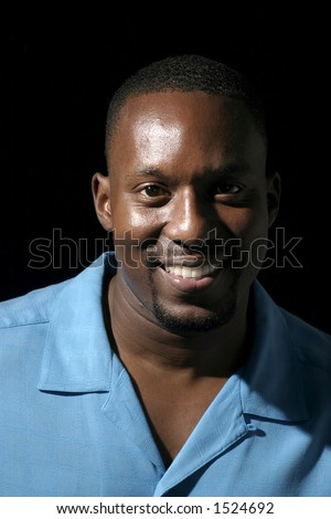 Low key portrait headshot on black background of a handsome smiling African American male. - stock photo