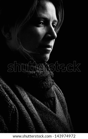 Low key portrait of a depressed woman - stock photo