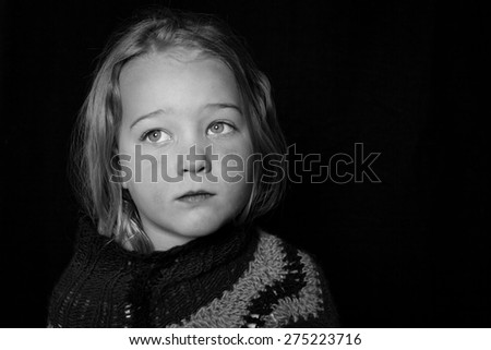 Low key Portrait of a young child. Sad looking girl. - stock photo