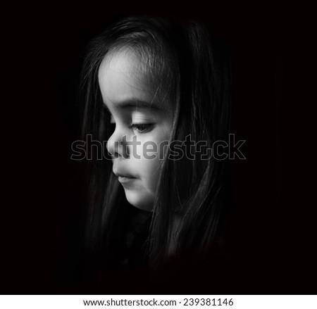 Low key Portrait of a young child. Sad looking girl is looking down.Picture is black and white. - stock photo