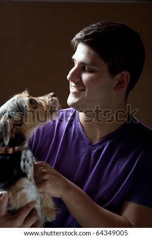 Low key portrait of a young man holding a cute mixed breed terrier dog isolated over a dark background. - stock photo