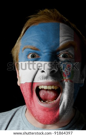 Low key portrait of an angry man whose face is painted in colors of dominican republic flag