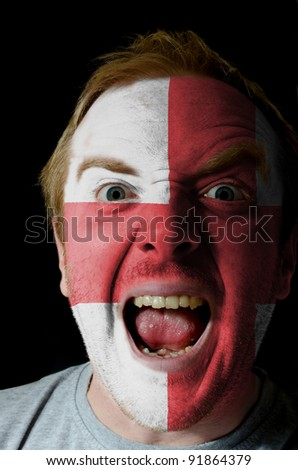 Low key portrait of an angry man whose face is painted in colors of el salvador flag